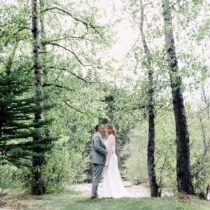 couple kissing in the forest in outdoor wedding